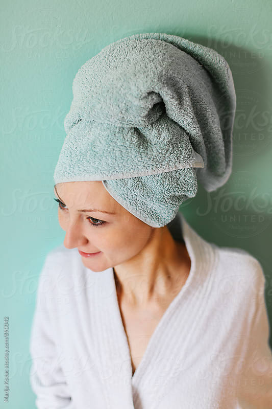 Young woman wearing a bathtowel and robe by Marija Kovac for Stocksy United