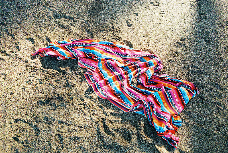 bright colored beach blanket on sand by wendy laurel for Stocksy United