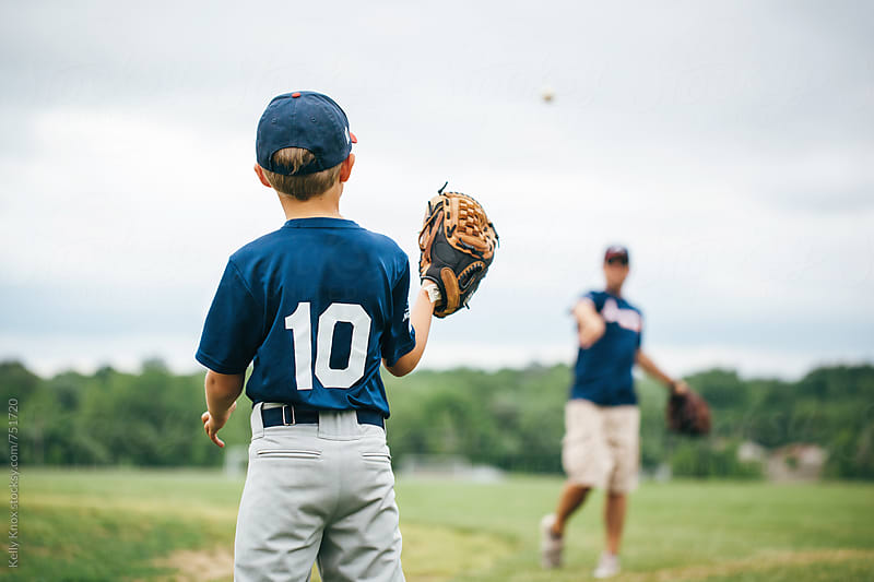 baseball player playing catch with his coach/father  by Kelly Knox for Stocksy United