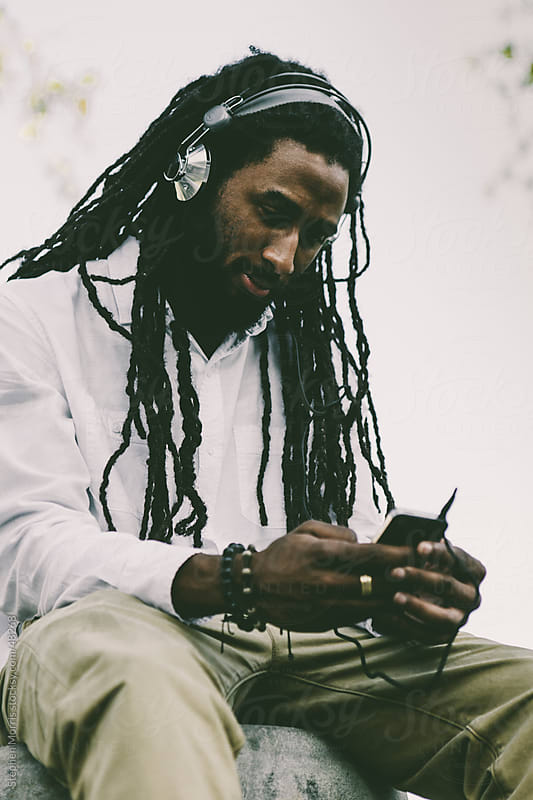 Young Man with Dreadlocks Using Headphones and Smart Phone by Stephen Morris for Stocksy United