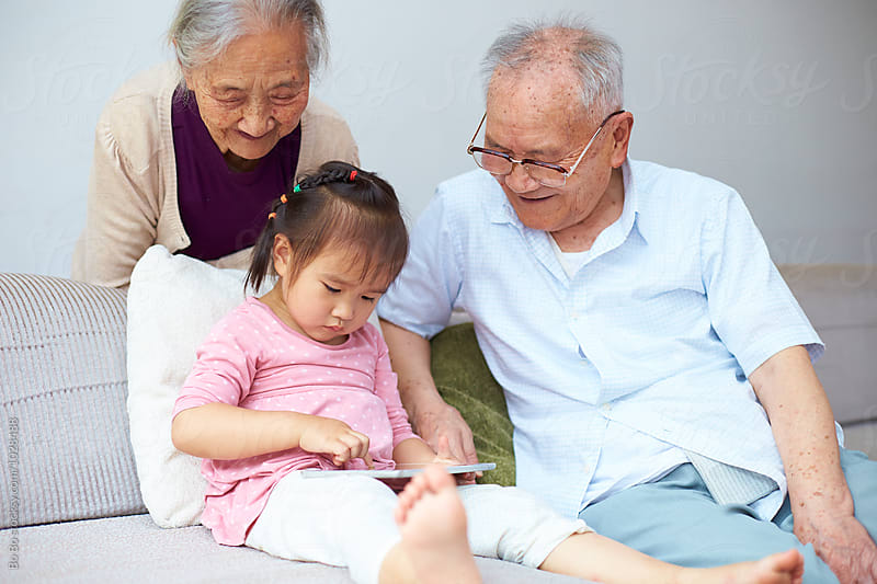 little asian girl using tablet indoor with her great grandparents by Bo Bo for Stocksy United