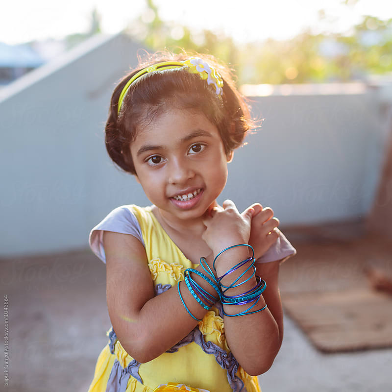 Portrait of little girl showing her blue bangles by Saptak Ganguly for Stocksy United