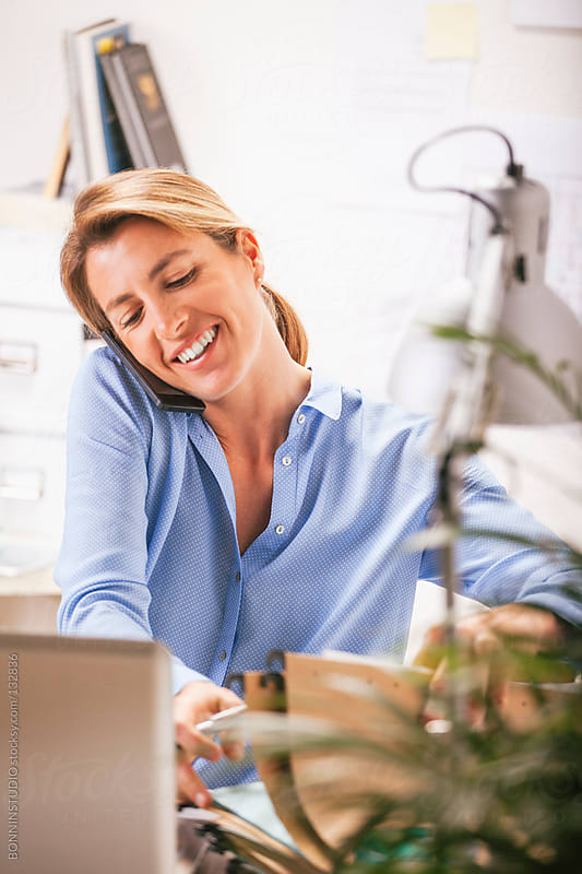 Beautiful mature business woman calling with mobile phone at home office. by BONNINSTUDIO for Stocksy United