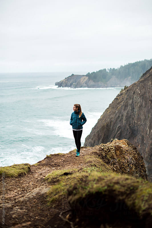 Young woman on the edge of a very steep cliff looking out over the ocean. by Kate Daigneault for Stocksy United