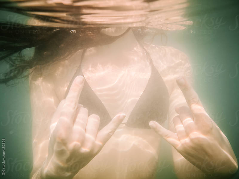 Young woman showing rock and roll gesture underwater by GIC for Stocksy United