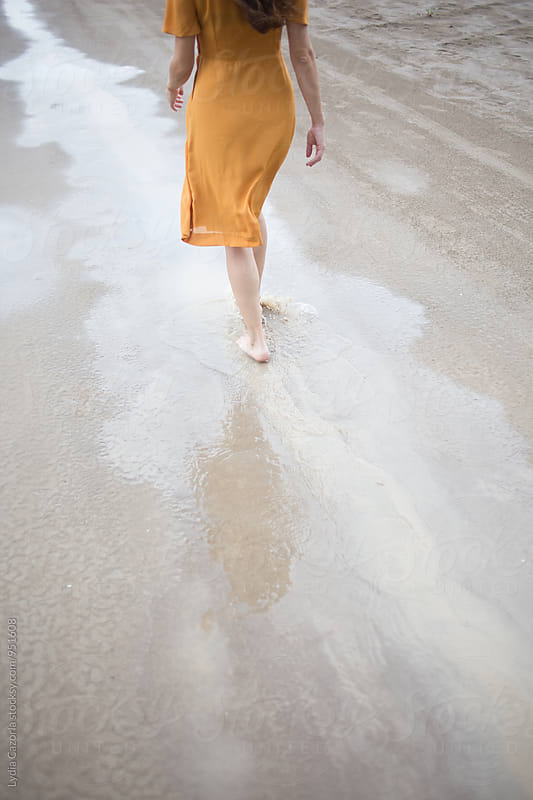 Young happy woman walking on the beach by Lydia Cazorla for Stocksy United