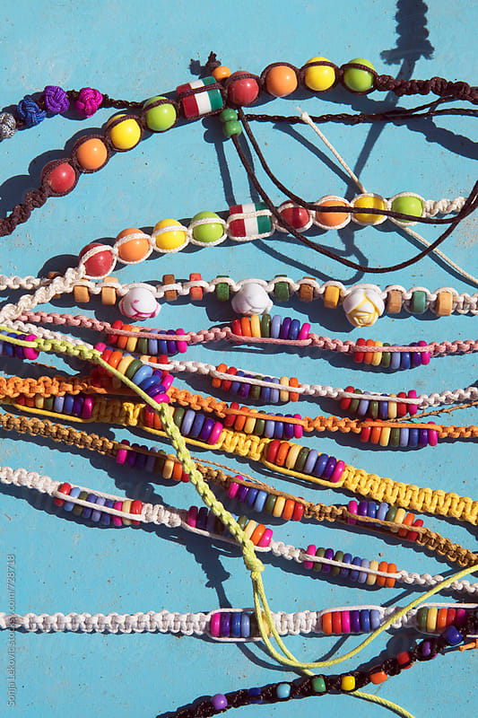 colorful summer bracelets on blue background by Sonja Lekovic for Stocksy United
