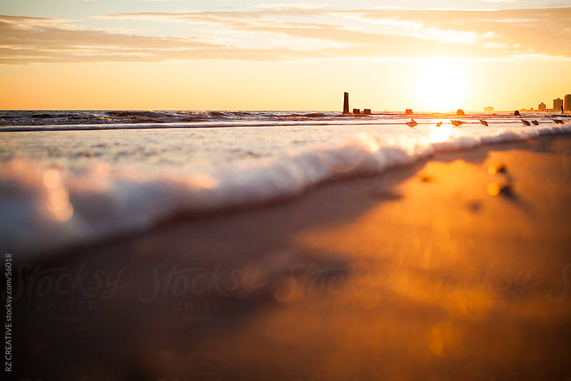 Low-angle picture of sand and waves at sunset. by Robert Zaleski for Stocksy United