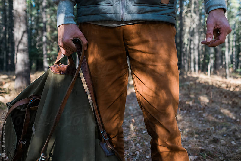 A man holds an old canvas & leather bag while standing in the woods. by Riley J.B. for Stocksy United
