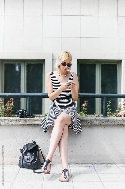 Blonde woman sitting and looking at her smart phone by Marija Kovac for Stocksy United