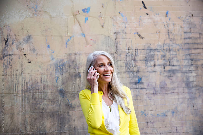 A woman talking on her smart phone by Ann-Sophie Fjelloe-Jensen for Stocksy United