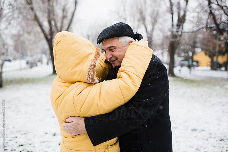 Old couple hugging outdoors in snowfall by Jovana Rikalo for Stocksy United