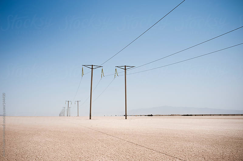 Electric power line  in the desert. by Jean-Claude Manfredi for Stocksy United