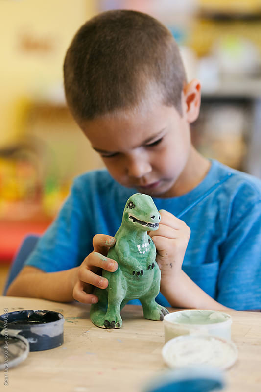 Boy Having Fun Painting Ceramic Dinosaur by Sean Locke for Stocksy United
