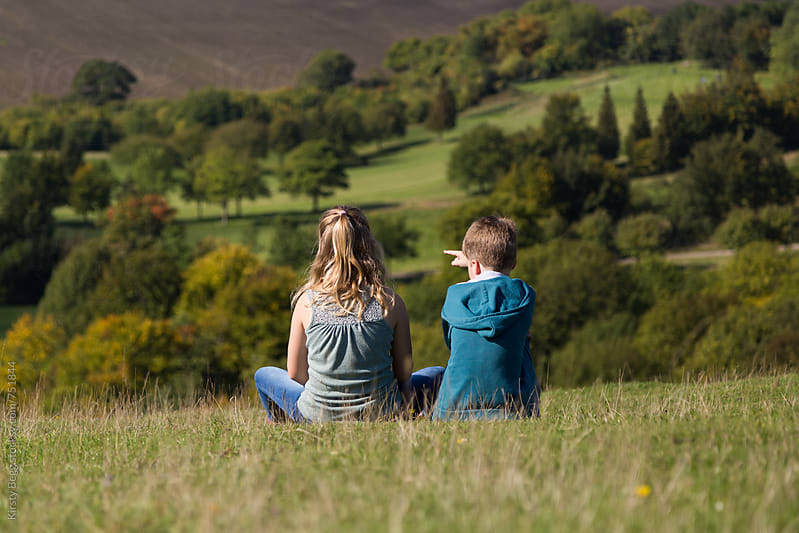 Boy and girl sitting on a hill looking a view of countrywide below by Kirsty Begg for Stocksy United