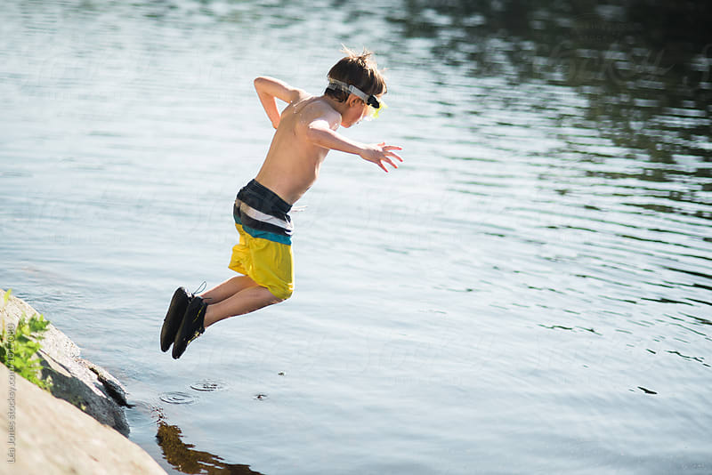 little boy jumping in a lake by Léa Jones for Stocksy United