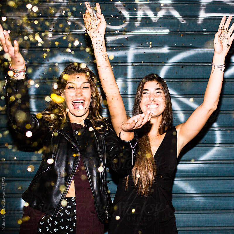 Smiling women throw confetti by michela ravasio for Stocksy United