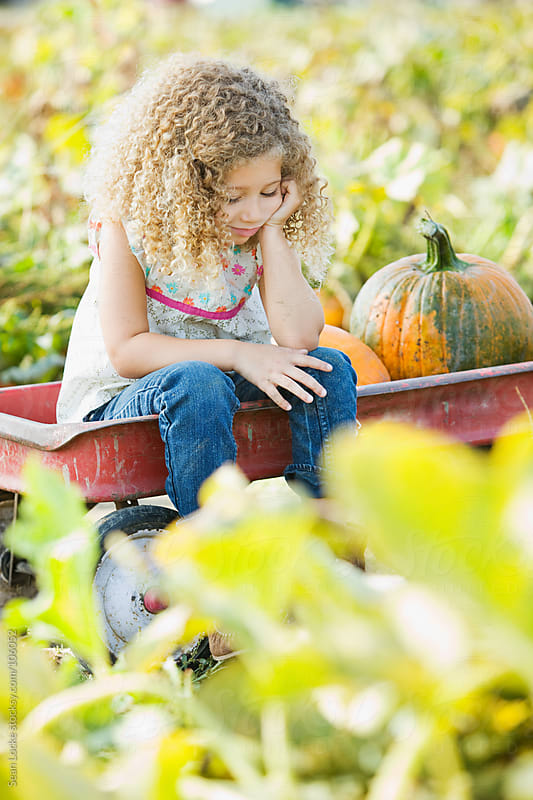 Pumpkins: Girl Waiting For Rest of Family by Sean Locke for Stocksy United