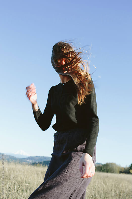 woman in a windy field on a sunny day with long hair in her face by KATIE + JOE for Stocksy United