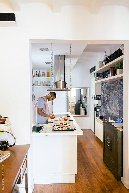Side view of a man preparing a handmade Italian pizza at home. by BONNINSTUDIO for Stocksy United