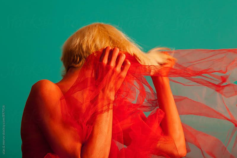 abstract portrait of young blond woman painted red and covered with a tulle by Ulaş and Merve for Stocksy United