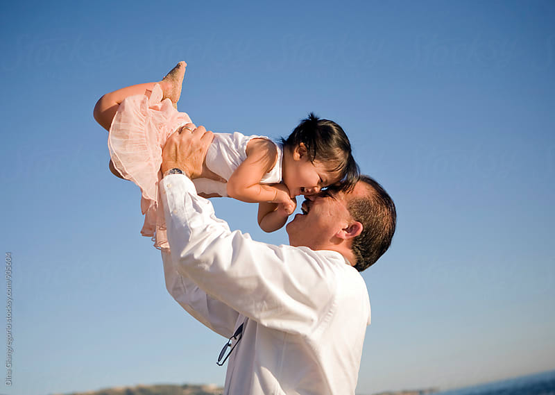 Asian Father Holding Daughter In Air by Dina Giangregorio for Stocksy United