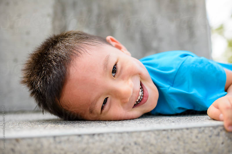 Cheerful little boy smiling while lying on stone ground by Lawren Lu for Stocksy United