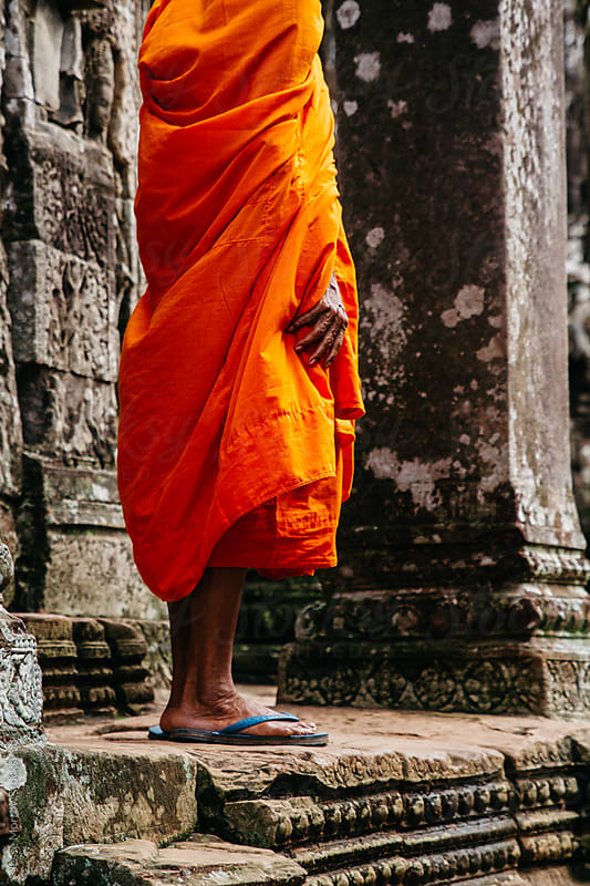 Monk stands in front of temple holding robe by Jesse Morrow for Stocksy United