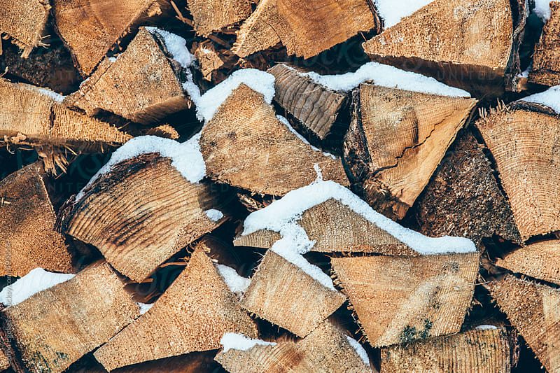 Pile of stacked fire wood with fresh snow on top by Soren Egeberg for Stocksy United