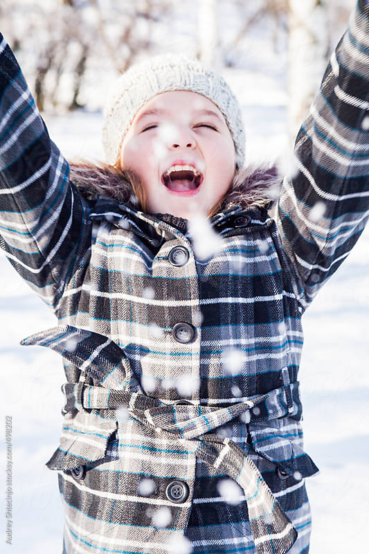 Smiling girl playing and smiling in the snow. by Audrey Shtecinjo for Stocksy United