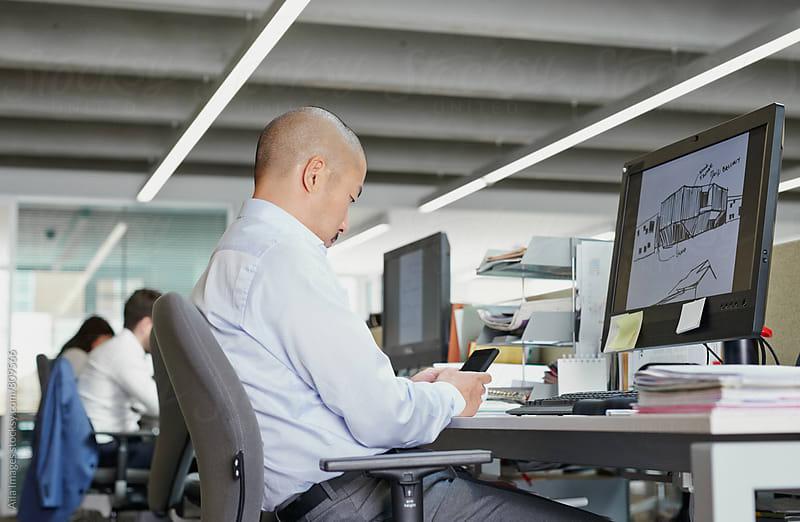 Japanese businessman using mobile phone multitasking at desk by Aila Images for Stocksy United