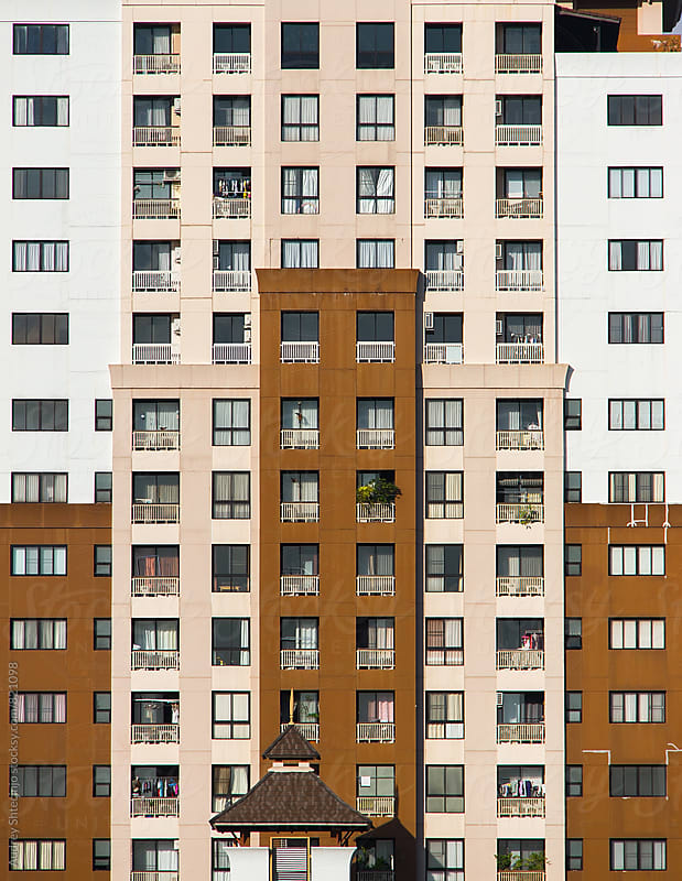 Building exterior with many apartment windows. by Audrey Shtecinjo for Stocksy United