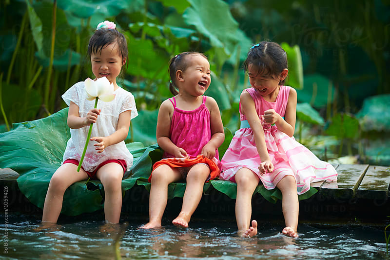 Three little girls sitting by the pond playing water by Bo Bo for Stocksy United