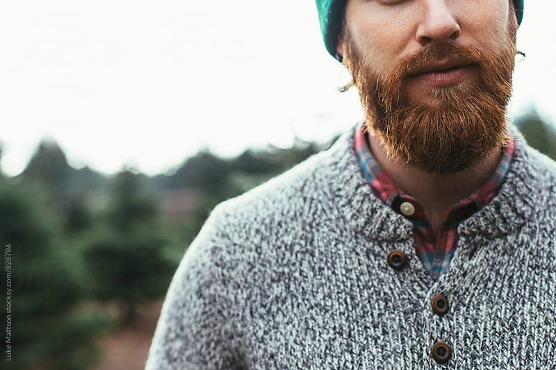 Bearded Man Wearing Green Beanie And Wool Sweater Over Red Flannel At Christmas Tree Farm by Luke Mattson for Stocksy United