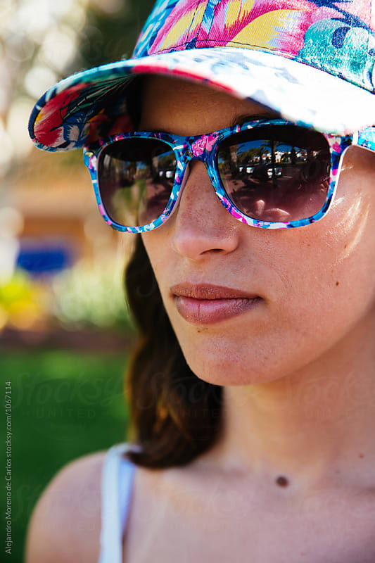 headshot of young woman in cap and sunglasses by Alejandro Moreno de Carlos for Stocksy United