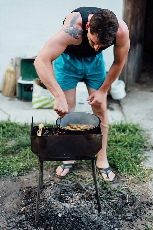 Man preparing a bbq in the yard by Boris Jovanovic for Stocksy United