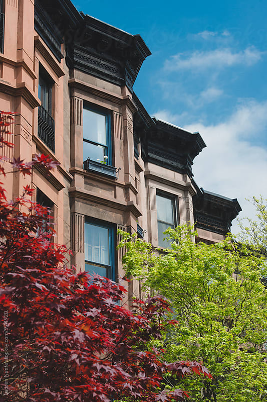 Brownstone buildings against a blue sky by Lauren Naefe for Stocksy United