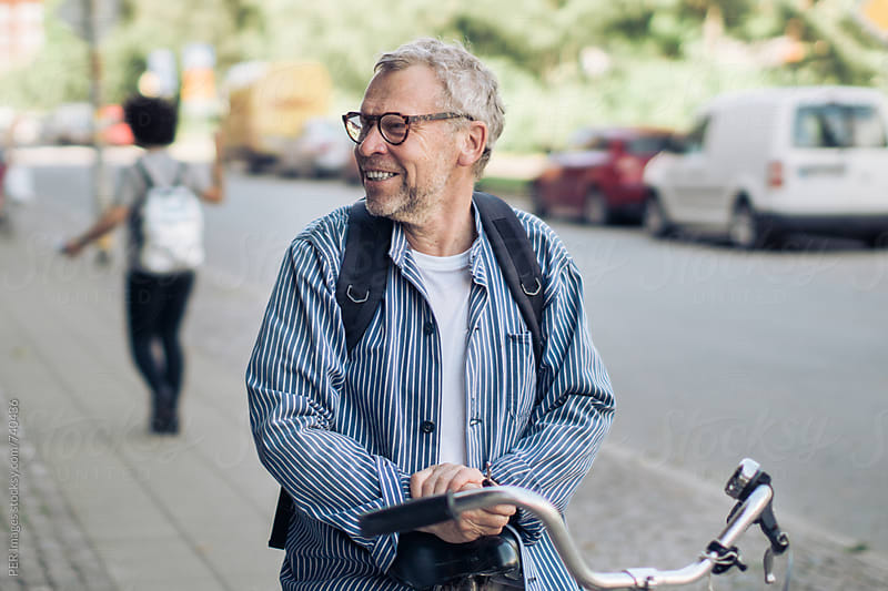 Happy senior man with his bicycle by Per Swantesson for Stocksy United