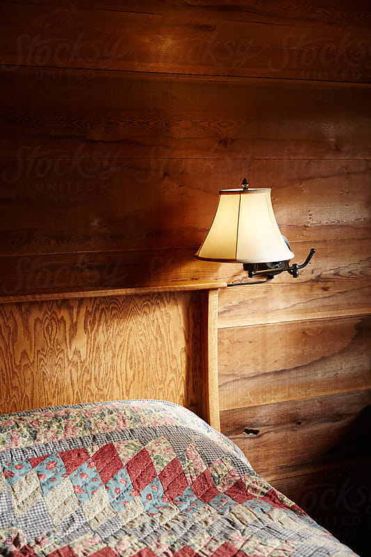 Bedroom inside rustic wood cabin by Trinette Reed for Stocksy United