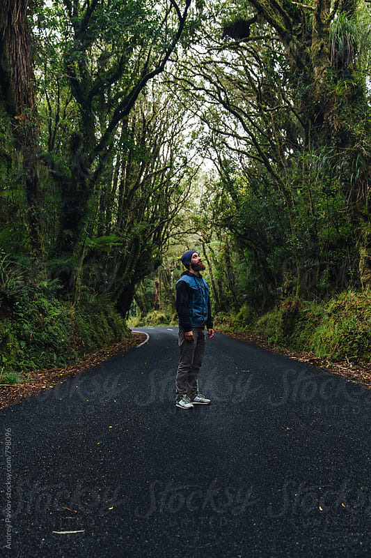 Man standing alone on secluded road by Andrey Pavlov for Stocksy United