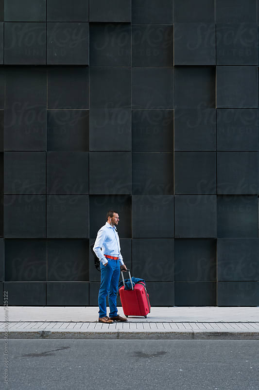 Businessman with the suitcase standing at the city street by Jelena Jojic Tomic for Stocksy United