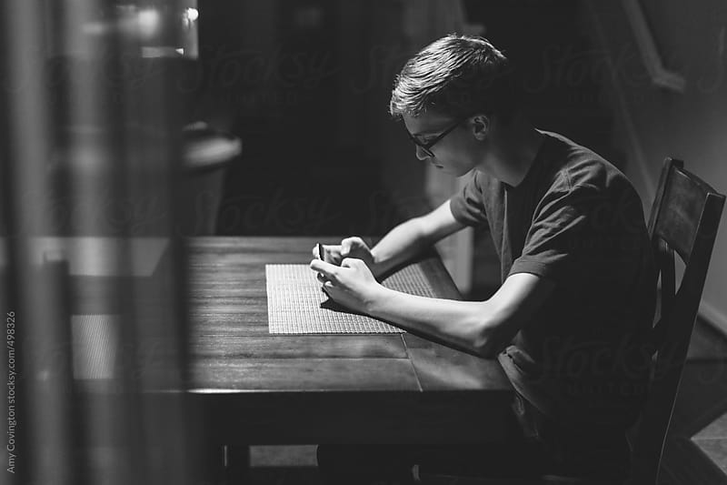 Teenage boy texting at night by Amy Covington for Stocksy United