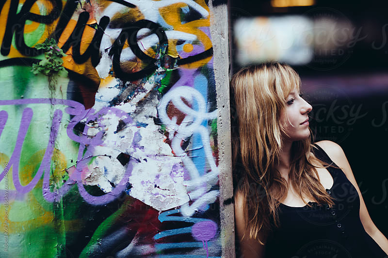 Girl at graffiti wall by Robert Kohlhuber for Stocksy United