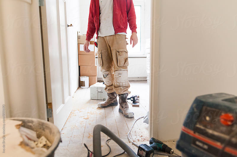 A worker or handyman standing in the mess of a renovation or restauration by Ivo de Bruijn for Stocksy United