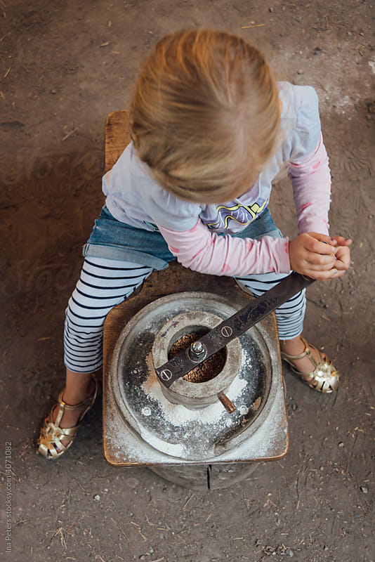 Food: Girl milling spelt in an ancient stone mill by Ina Peters for Stocksy United