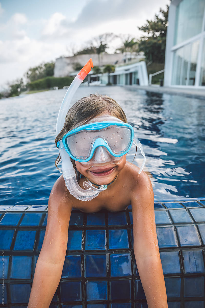 portrait of young boy with snorkeling gear in a big swimming ...