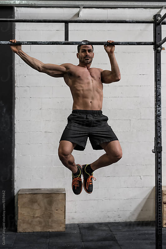 Man doing pull-ups  by Guille Faingold for Stocksy United