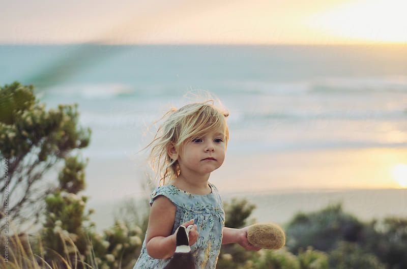 Little girl playing by the beach by Dominique Chapman for Stocksy United