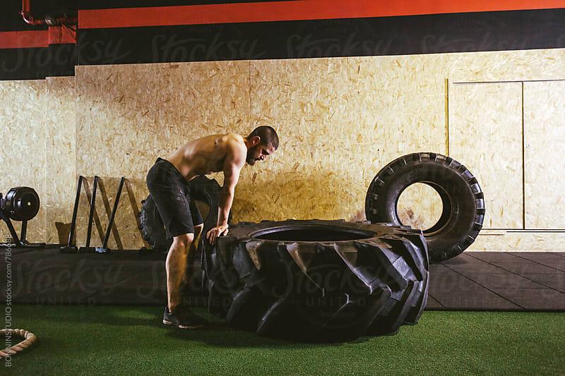 Man lifting a heavy tire in a gym box. by BONNINSTUDIO for Stocksy United