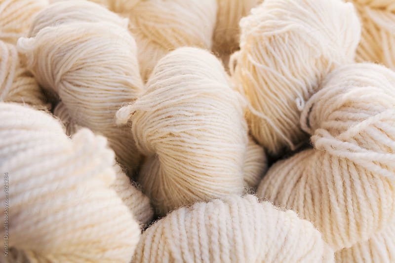 Skeins of white woolen yarn by Kristin Duvall for Stocksy United